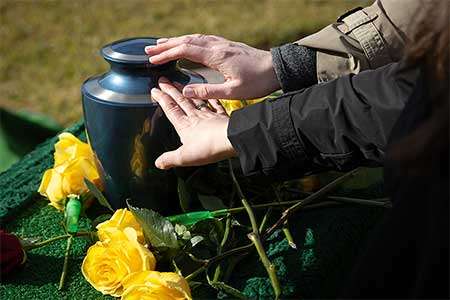 Humanist funeral ceremonies - photo of hands rested on urn